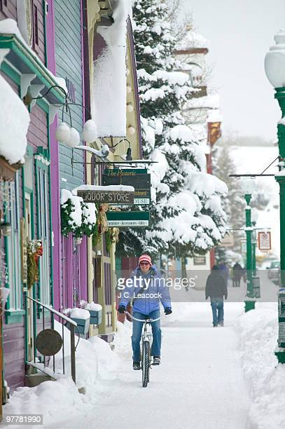 Woman riding a bike down snow covered Elk Avenue, Crested Butte, Colorado.