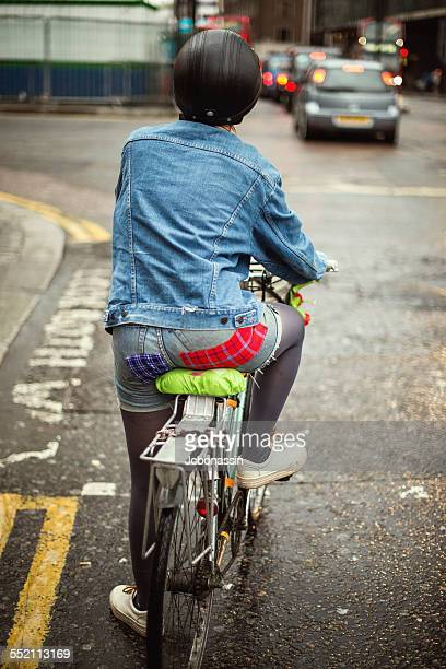 woman riding a bike in london - jcbonassin stock pictures, royalty-free photos & images