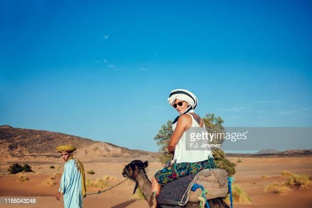 woman riding a camel in the desert erg chebbi, morocco - femme touareg photos et images de collection
