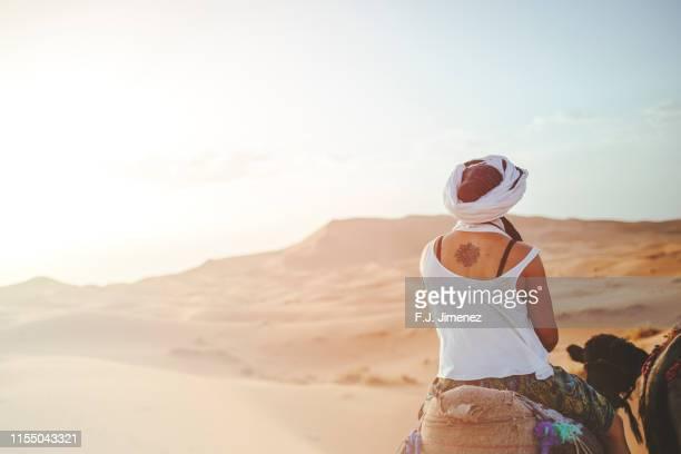 woman riding a camel in the desert of merzouga - femme touareg photos et images de collection