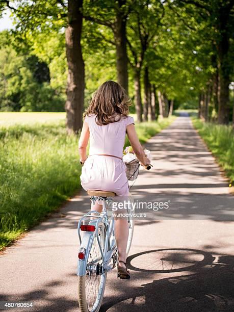 Mulher que monta um clássico de bicicleta através de um parque viçosa