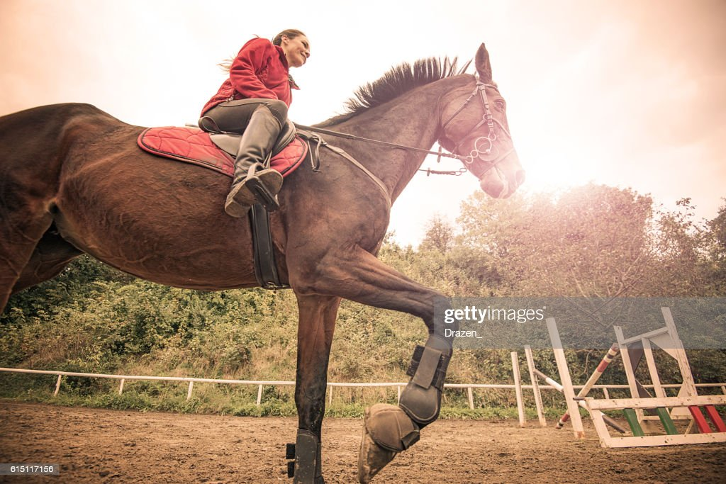 Woman Riding A Galloping Horse Stock Photo