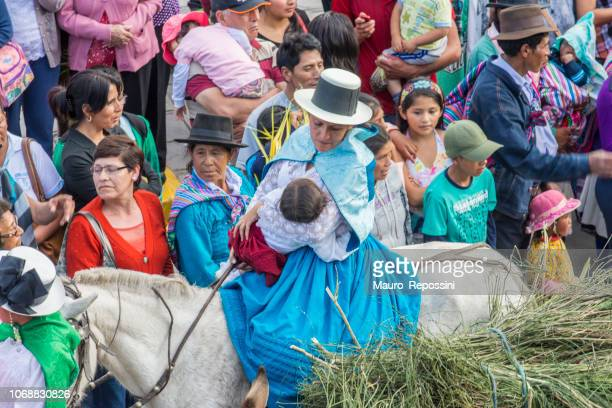 woman riding a horse and holding a baby during the celebration of the palm sunday of easter at ayacucho city. peru. - horse easter stock pictures, royalty-free photos & images