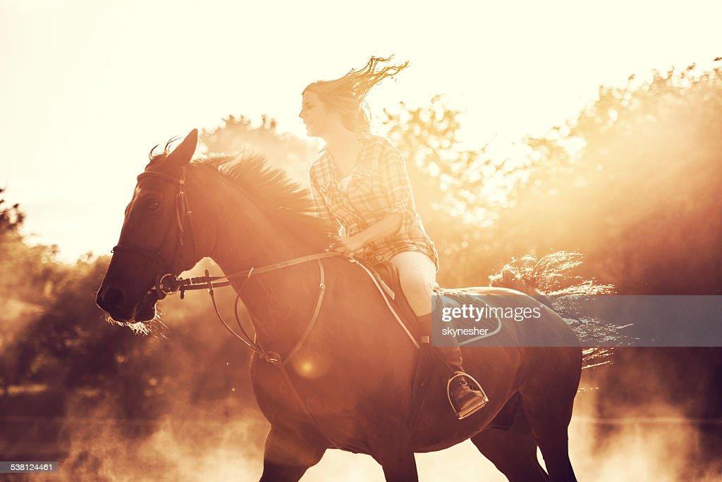 Woman riding a stallion outdoors. : Stock Photo