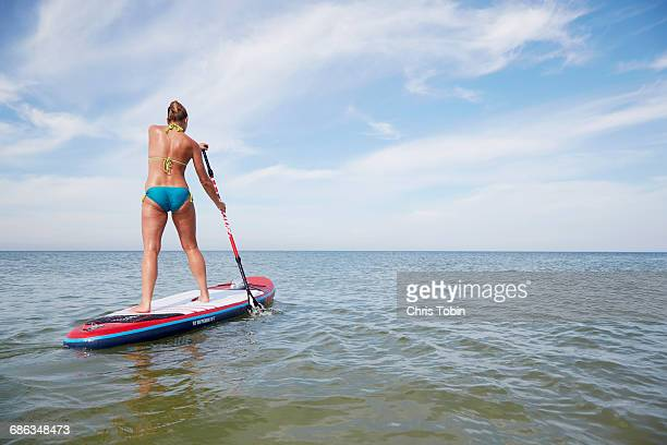 Woman riding a stand up paddle board