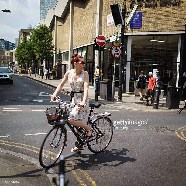 Woman riding a traditional Bicycle with a basket, in the summer, on the street in Brick Lane, Shoreditch, London. Wearing summer dress at a road...