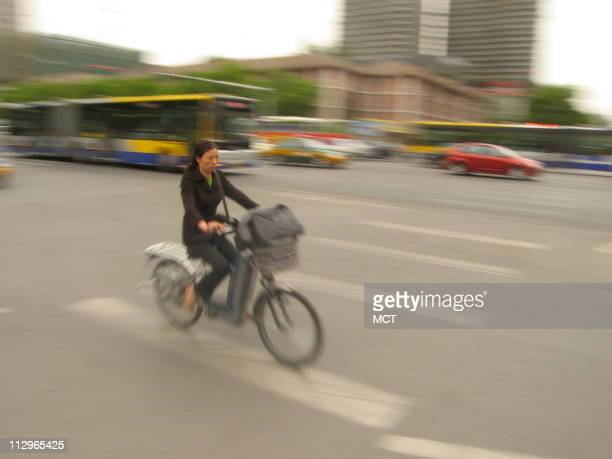A woman riding an electric bicycle whizzes through an intersection in Beijing China where ebicycles are increasingly common
