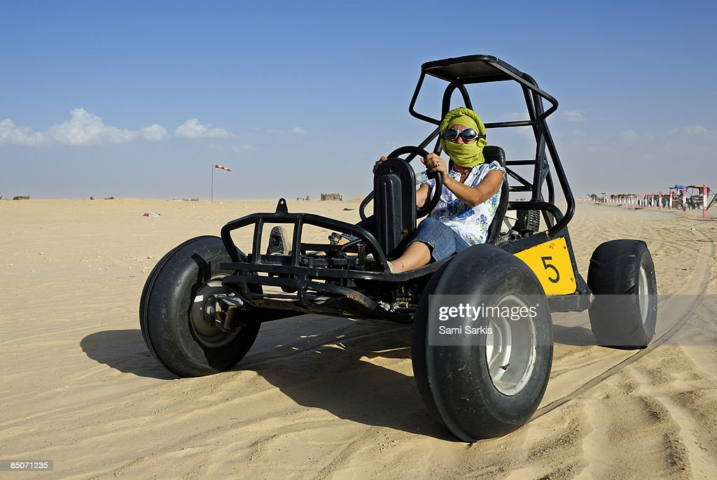 Woman riding beach buggy in desert : Stock Photo