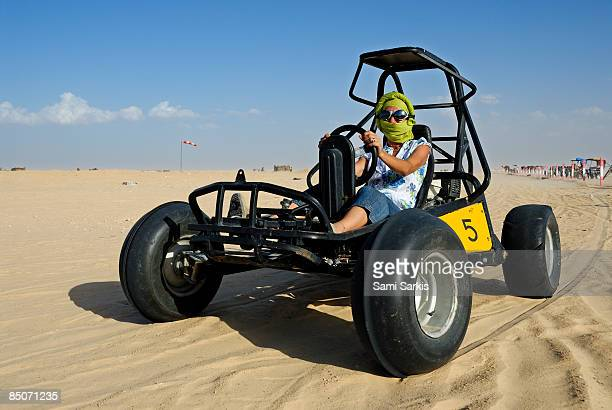 Woman riding beach buggy in desert
