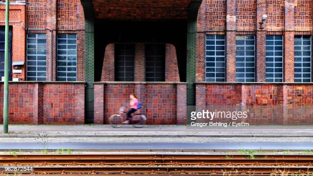 Woman Riding Bicycle Against Building On Road