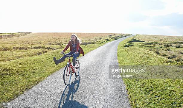 Woman riding bicycle along road in countryside.