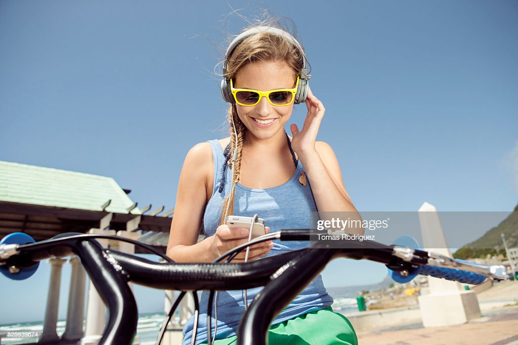 Woman riding bicycle and listening to music on smart phone : Foto de stock