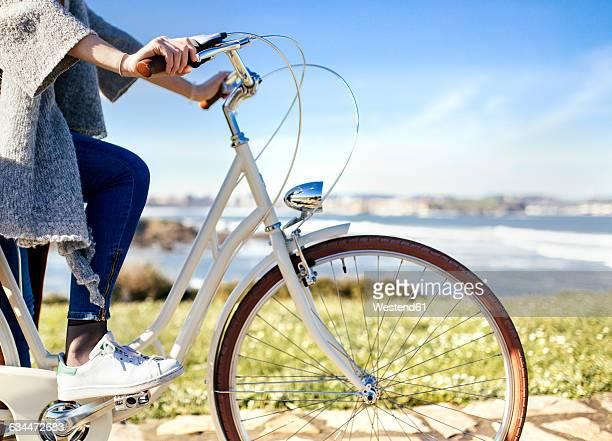 woman riding bicycle at the coast - ヒホン ストックフォトと画像