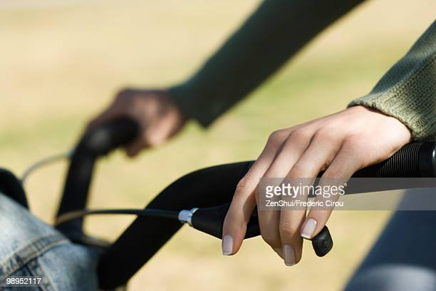 Woman riding bicycle, cropped view