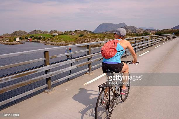 Woman riding bicycle in Solund Islands, Norway