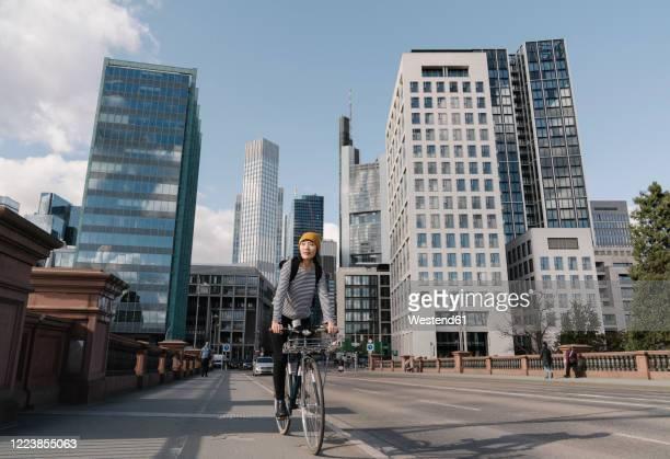 woman riding bicycle in the city, frankfurt, germany - hesse duitsland stockfoto's en -beelden