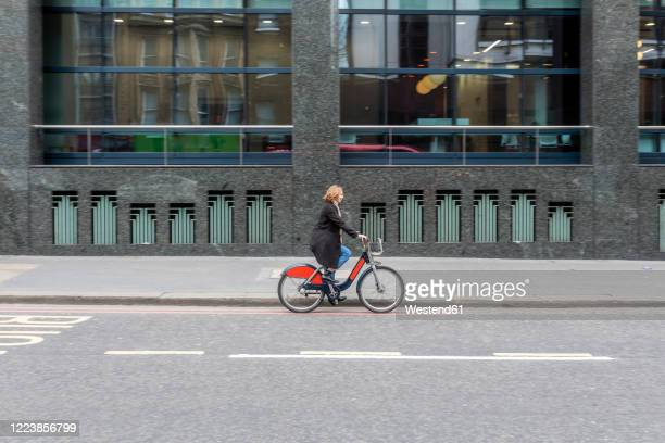 woman riding bicycle in the city, london, uk - side view stock pictures, royalty-free photos & images