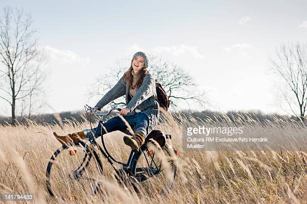 Woman riding bicycle in wheatfield