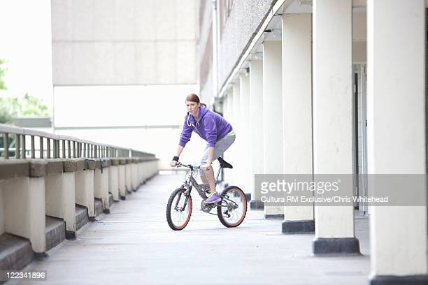 woman riding bicycle on city street - newpremiumuk stock pictures, royalty-free photos & images