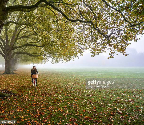 Woman Riding Bicycle On Grass By Trees In Park During Autumn