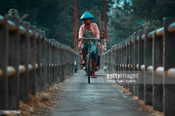 woman riding bicycle on railing - indonesia stock pictures, royalty-free photos & images