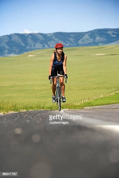 woman riding bicycle on road - sportlerin stock-fotos und bilder