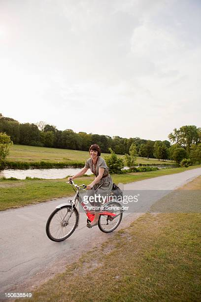woman riding bicycle on rural road - pedalantrieb stock-fotos und bilder