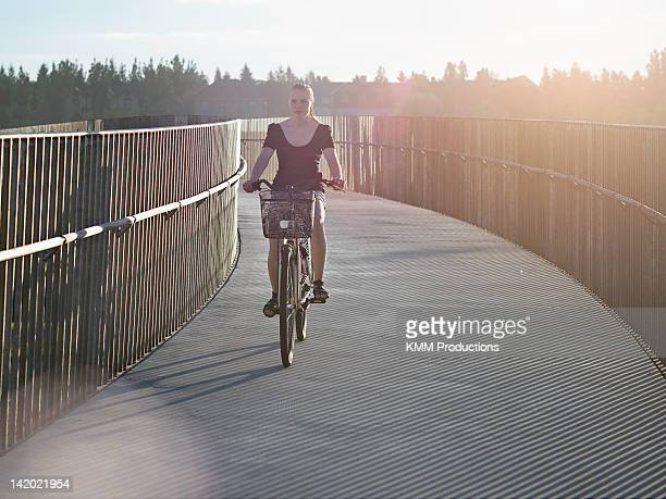 Woman riding bicycle on skybridge