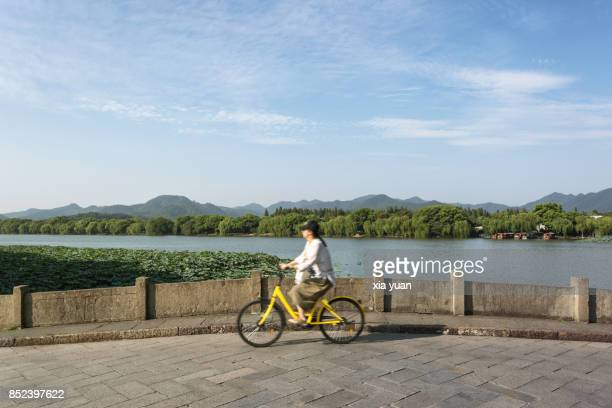 Woman riding bicycle on stone bridge over West Lake,Hangzhou,China