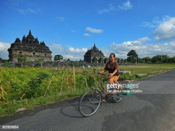 woman riding bicycle on street against sky - tian abdul hanip stock photos and pictures