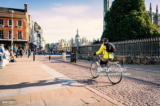 woman riding bicycle on street in city - cambridge stock pictures, royalty-free photos & images