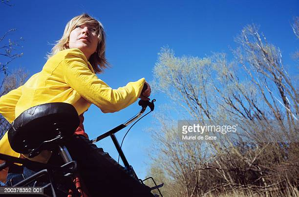Woman riding bicycle outdoors, low angle view