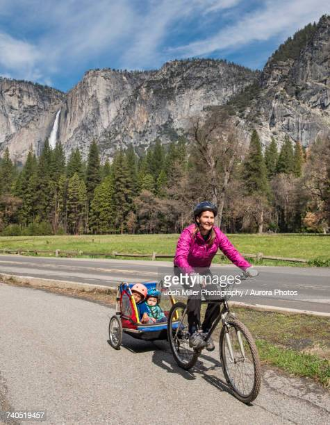 Woman riding bicycle with children in Yosemite National Park