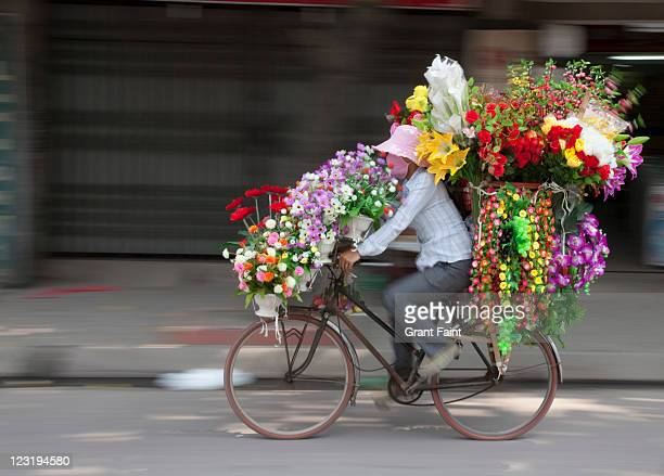 Woman riding bicycle with flowers.