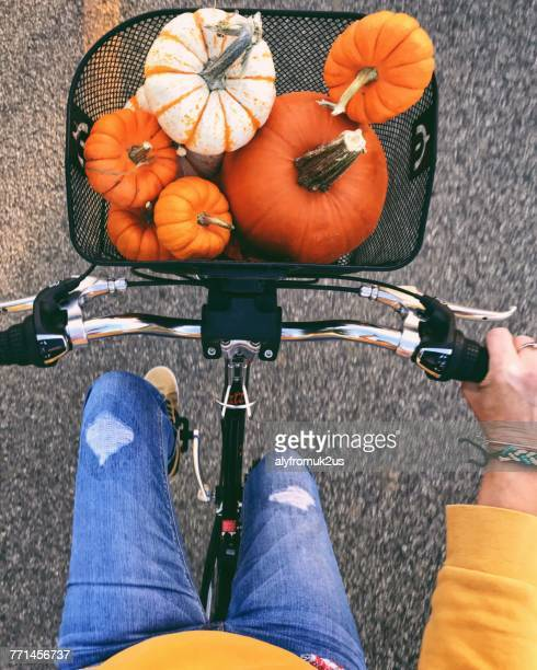 Woman riding bicycle with pumpkins in the basket