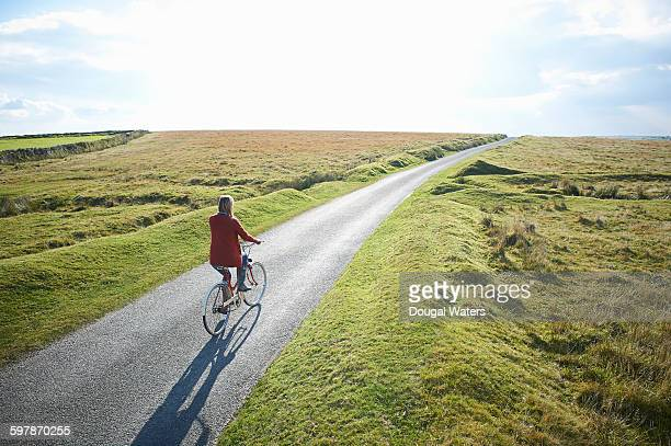 woman riding bike along country lane. - long hair stock pictures, royalty-free photos & images