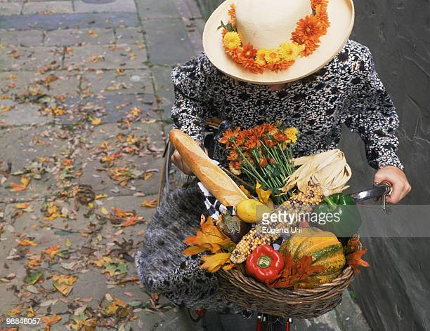 Woman riding bike carrying basket of vegetables