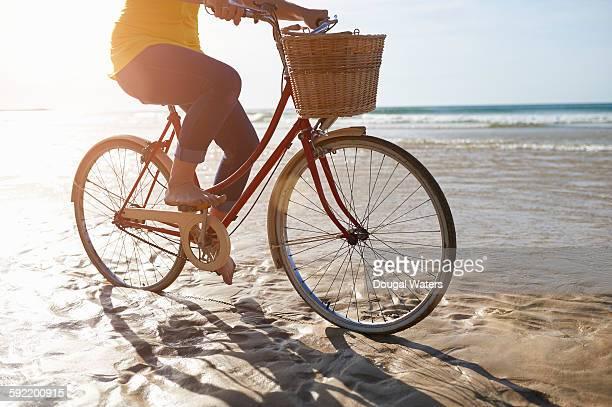 Woman riding bike on beach, close up.