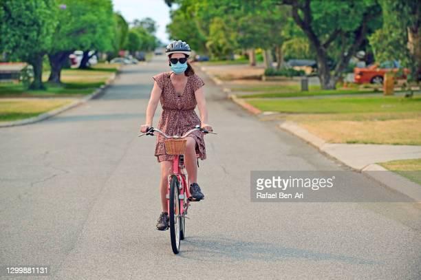 woman riding bike with face mask - rafael ben ari - fotografias e filmes do acervo