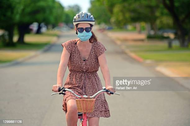 woman riding bike with face mask portrait - rafael ben ari - fotografias e filmes do acervo