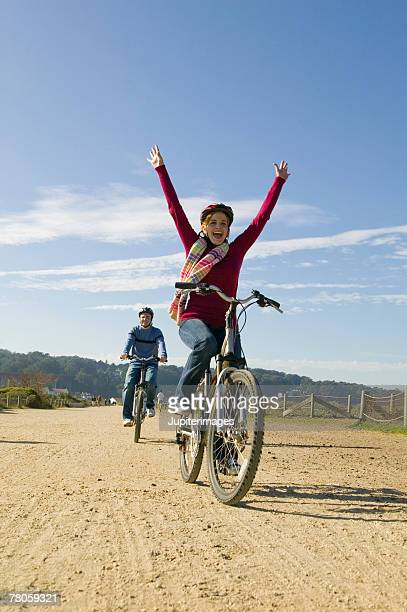 woman riding bike with no hands on handlebars - hands free cycling stock pictures, royalty-free photos & images