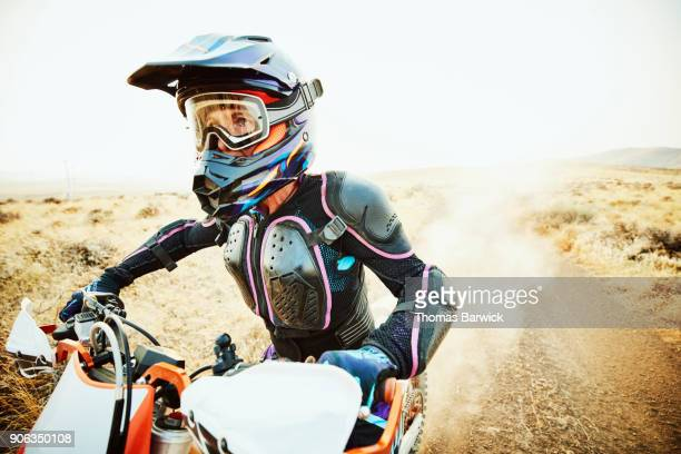 Woman riding dirt bike down desert road on summer evening