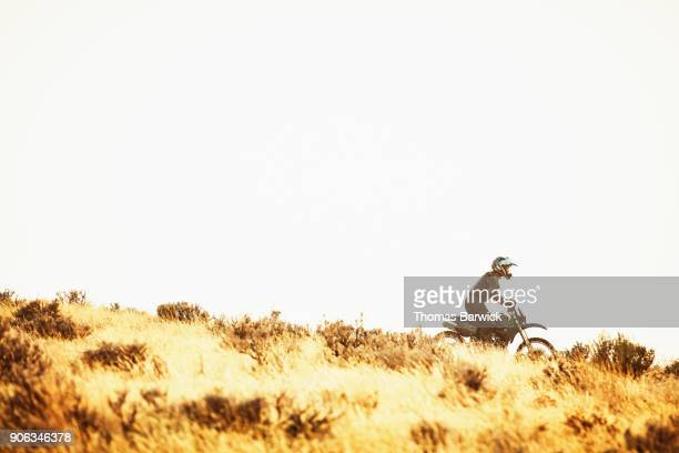Woman riding dirt bike down hill during desert ride on summer evening