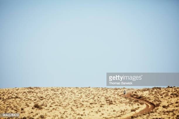 Woman riding dirt bike on desert road on summer afternoon