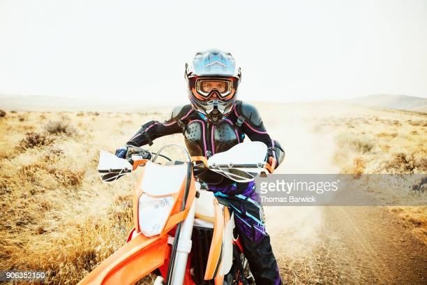Woman riding dirt bike on desert road on summer evening