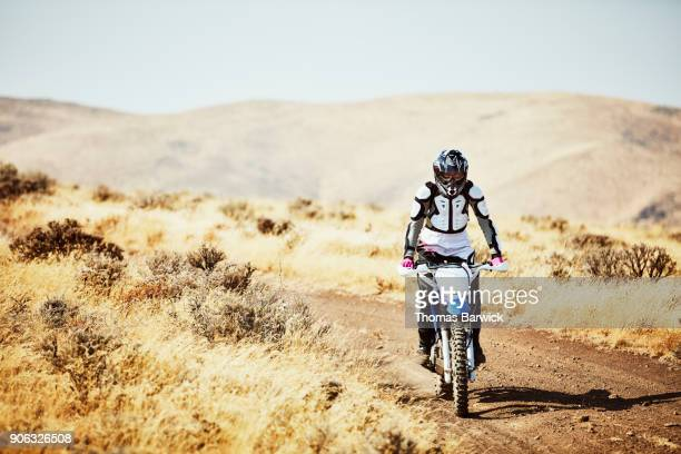 Woman riding dirt bike on desert road