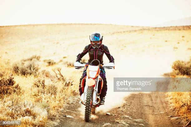 Woman riding dirt bike on dusty desert road on summer evening