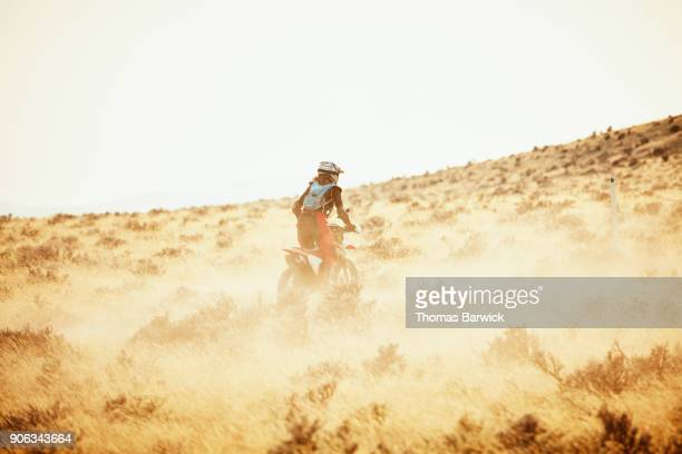 Woman riding dirt bike on dusty desert trail on summer evening