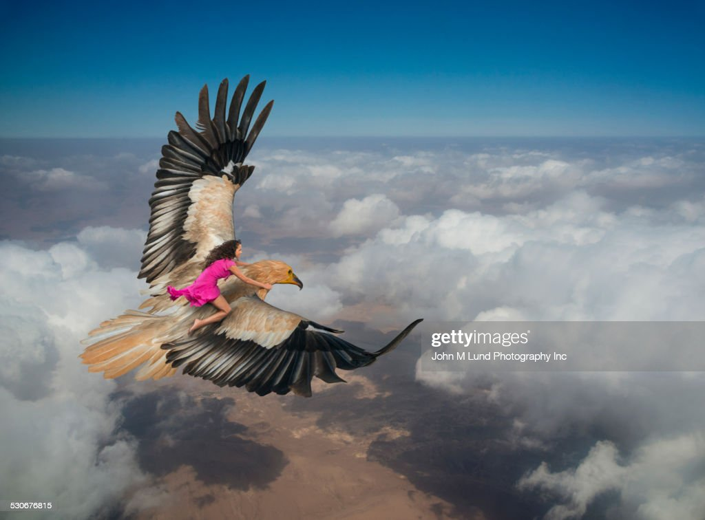 Woman riding eagle flying over clouds in sky : Foto de stock