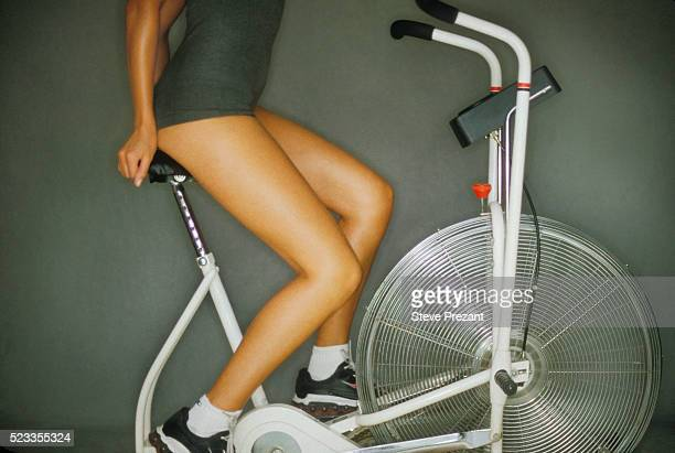 woman riding exercise bike - exercise bike stock photos and pictures